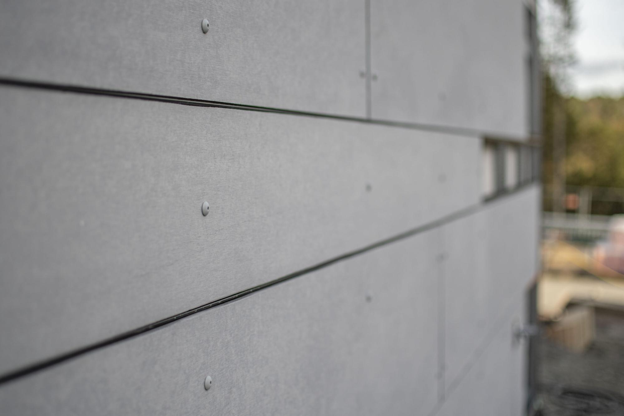 Grå fasad i närbild. Byggd av GDSB Bygg.
